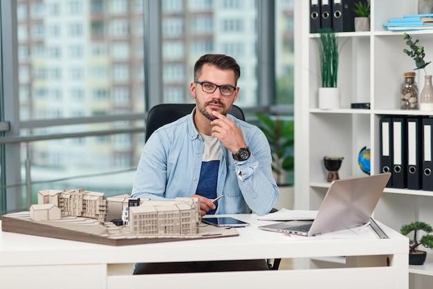 Arquiteto barbudo de sucesso concentrado em óculos sentado em seu local de trabalho com um layout de futuros edifícios