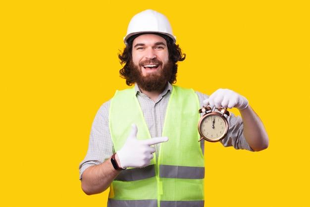 Arquiteto barbudo surpreso usando capacete e apontando para o despertador