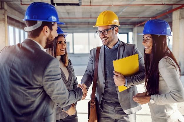 Arquiteto bem sucedido sorridente segurando uma pasta com o contrato em mãos e apertando as mãos do empresário. ao lado dele estão suas colegas. Foto Premium