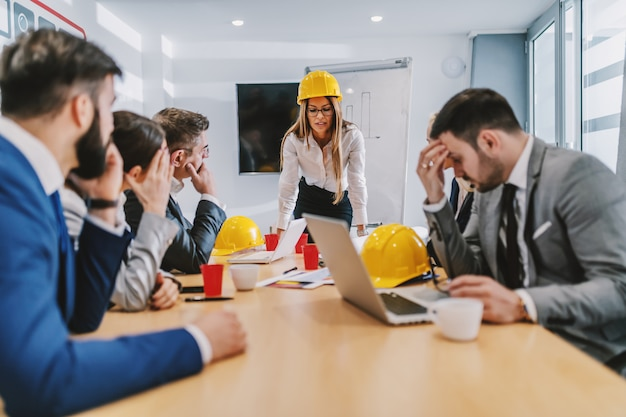 Arquiteto caucasiano atraente feminino encostado na mesa e olhando a papelada. colegas a escutando. existe um problema com o projeto.
