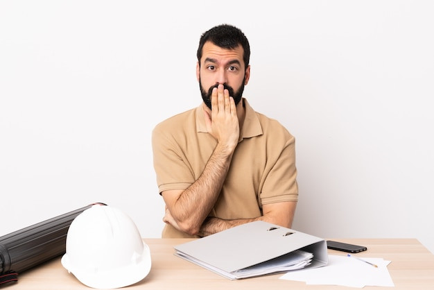 Arquiteto caucasiano homem com barba em uma mesa cobrindo a boca com a mão