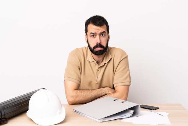 Arquiteto caucasiano homem com barba em uma mesa com expressão triste