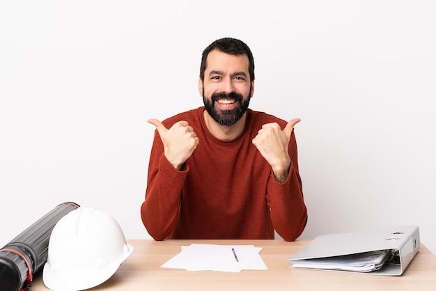 Arquiteto caucasiano homem com barba em uma mesa com polegares para cima gesto e sorrindo