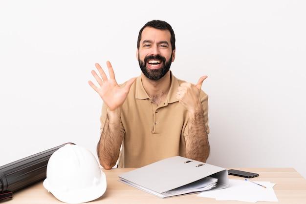 Arquiteto caucasiano homem com barba em uma mesa contando seis com os dedos
