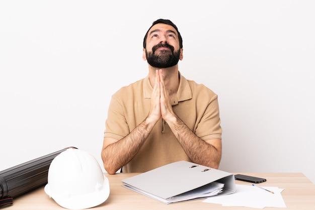 Arquiteto caucasiano homem com barba em uma mesa mantém palm juntos. pessoa pede algo