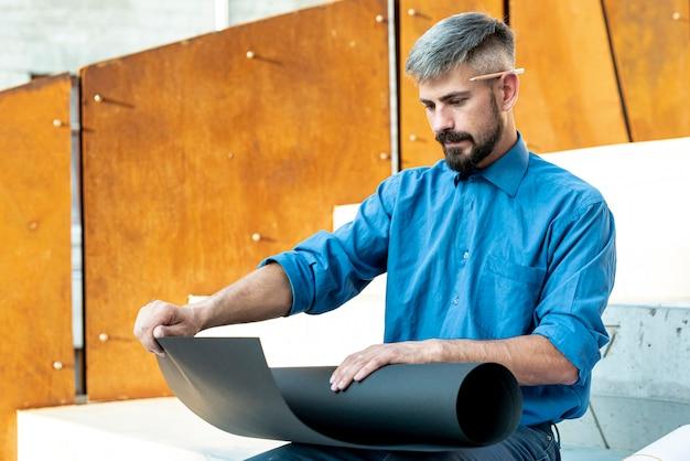 Arquiteto com camisa azul e esquemas