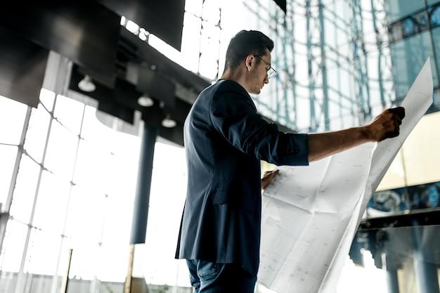 Arquiteto com roupas elegantes segura folha com desenho na mão e fala por telefone no fundo de um moderno edifício de vários andares de vidro.