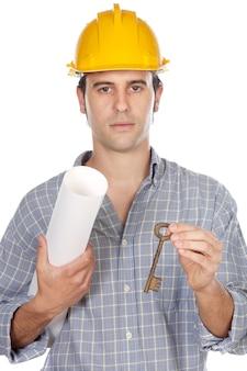 Arquiteto com uma chave um planos da casa na mão