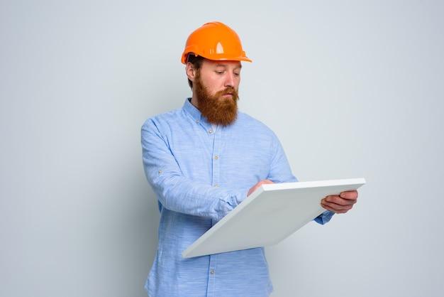Arquiteto confiante com barba e capacete laranja faz um esboço