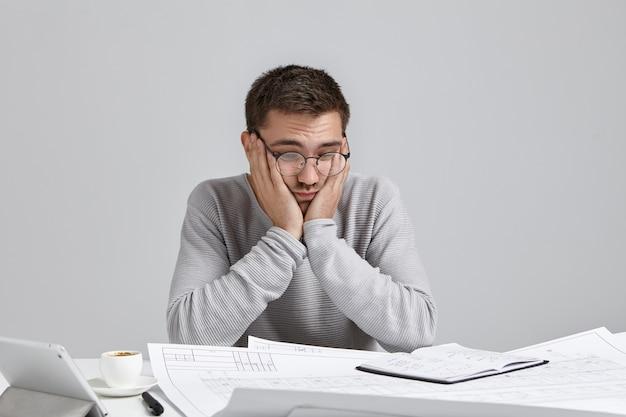 Arquiteto confuso comete erros, mantém a mão nas bochechas perplexo, parece cansado e cansado
