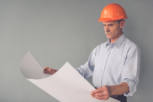 Arquiteto considerável no capacete protetor está estudando rascunhos