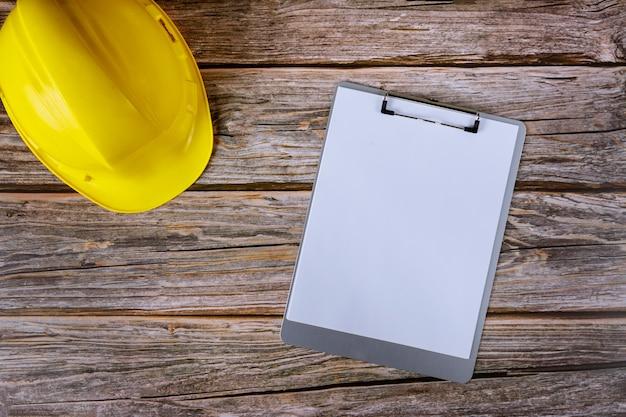 Arquiteto construtores manutenção escritório construção, capacete amarelo com o uso de bloco de notas de papel de parede na mesa de madeira.