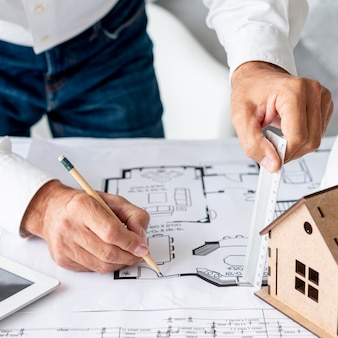 Arquiteto de alto ângulo, trabalhando em planos de construção