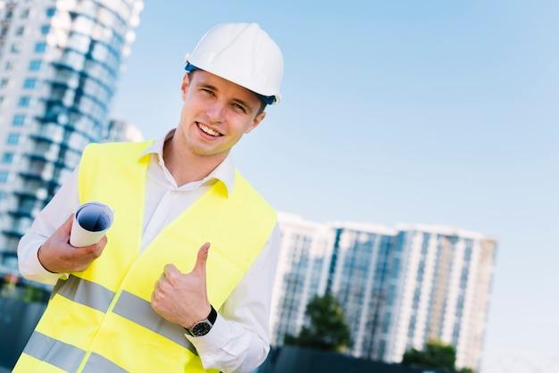 Arquiteto de baixo ângulo jovem com planos e capacete