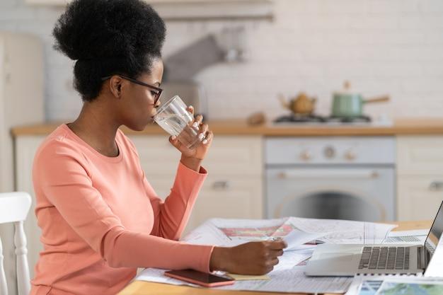 Arquiteto de designer de mulher negra freelance trabalhar em casa beber água usar laptop