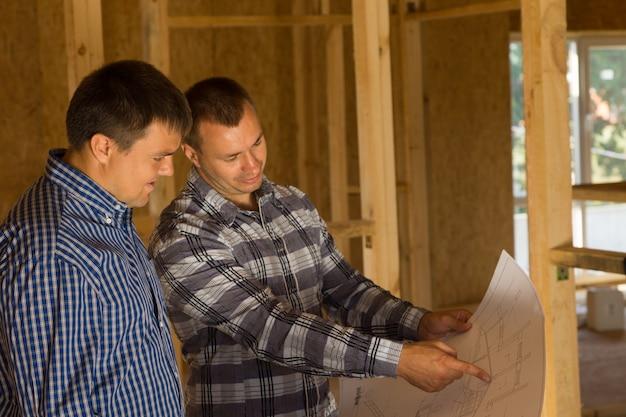 Arquiteto de edifício masculino profissional branco e cliente discutindo o design de construção de interiores no blue print.