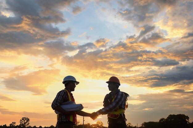 Arquiteto de engenharia civil de homem asiático usando capacete de segurança, reunido no local de construção. reunião de equipe de engenharia de arquitetura no local de trabalho.