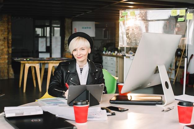 Arquiteto de jovem mulher de chapéu preto e jaqueta de lazer, trabalhando à mesa