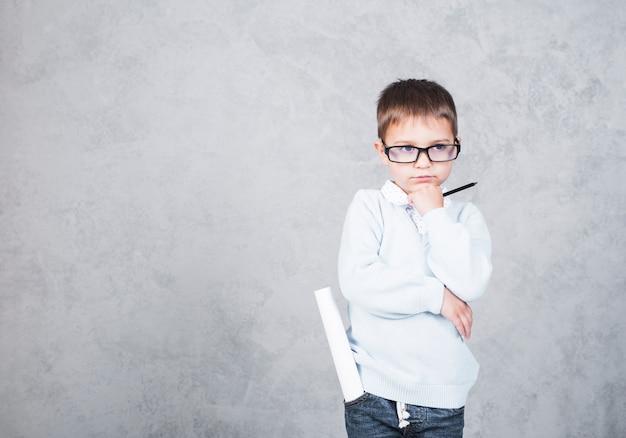Arquiteto de menino pensativo com rolo de papel no bolso
