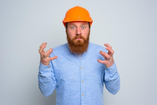 Arquiteto de raiva isolada com barba e capacete laranja