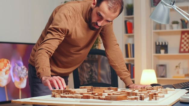 Arquiteto de sucesso trabalhando à noite em seu escritório em casa em um novo projeto de cidade.
