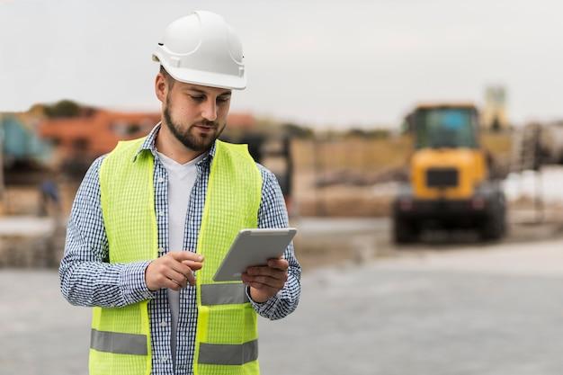 Arquiteto de tiro médio segurando um tablet