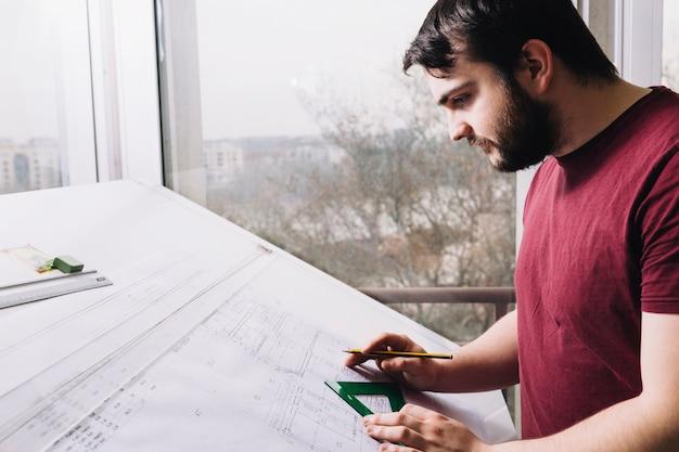 Arquiteto de vista lateral, desenhando plantas