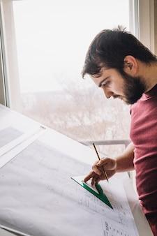 Arquiteto de vista lateral fazendo rascunhos