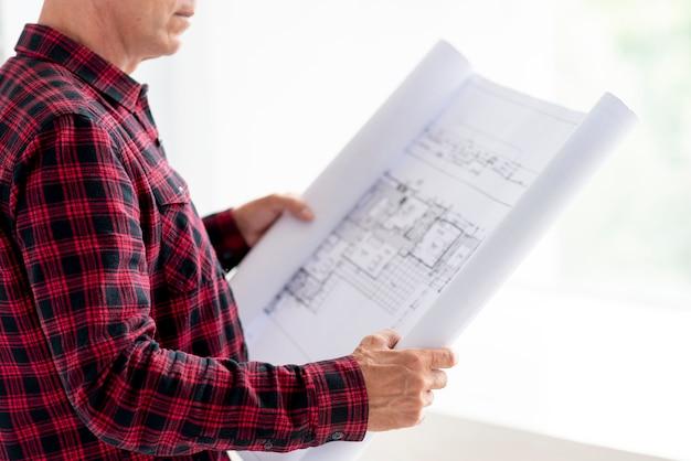 Arquiteto de vista lateral, verificando o projeto