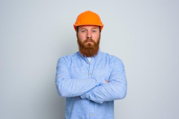 Arquiteto duvidoso isolado com barba e capacete laranja