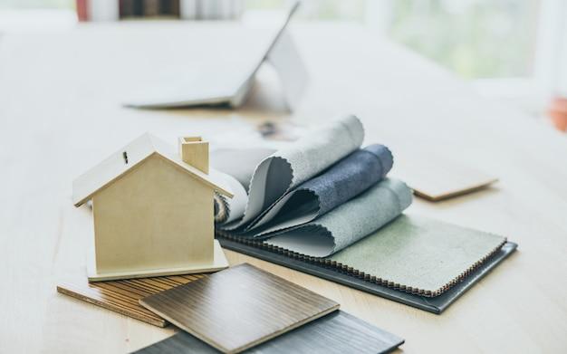 Arquiteto e desktop home do decorador interior com ferramentas, amostras de folha de madeira e decoração home do projeto.