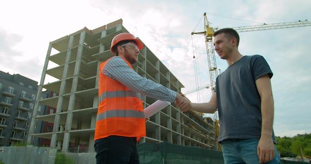 Arquiteto e engenheiro, apertando as mãos com a planta no canteiro de obras.