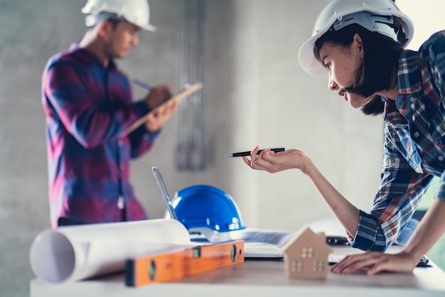 Arquiteto e engenheiro que trabalha o documento de desenho sobre o planejamento do projeto e o andamento do cronograma de trabalho no canteiro de obras,