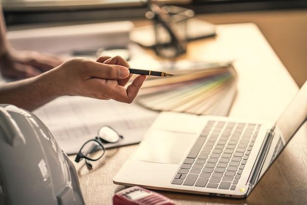 Arquiteto e engenheiro que trabalha o documento de desenho sobre o planejamento do projeto e o andamento do cronograma de trabalho no canteiro de obras