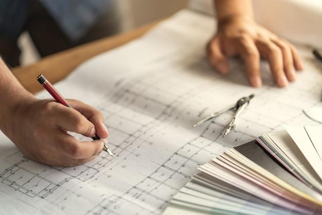 Arquiteto e engenheiro trabalhando documento de desenho sobre o planejamento do projeto e o andamento do cronograma de trabalho no canteiro de obras de construção civil
