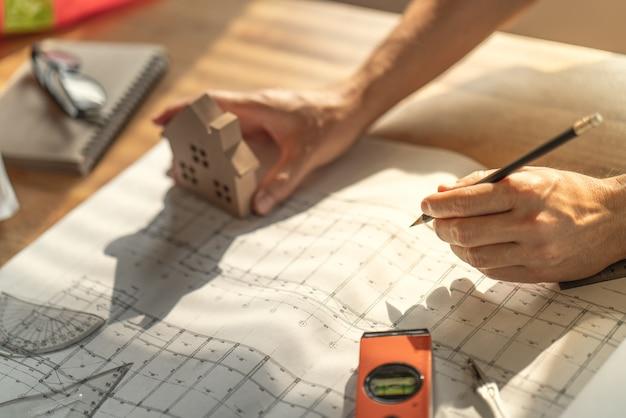 Arquiteto e engenheiro trabalhando documento de desenho sobre o planejamento do projeto e o andamento do cronograma de trabalho