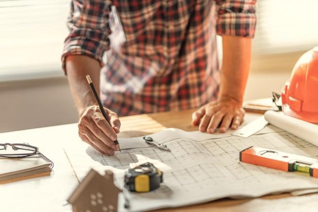 Arquiteto e engenheiro trabalhando documento de desenho sobre o planejamento do projeto e o andamento do cronograma de trabalho.