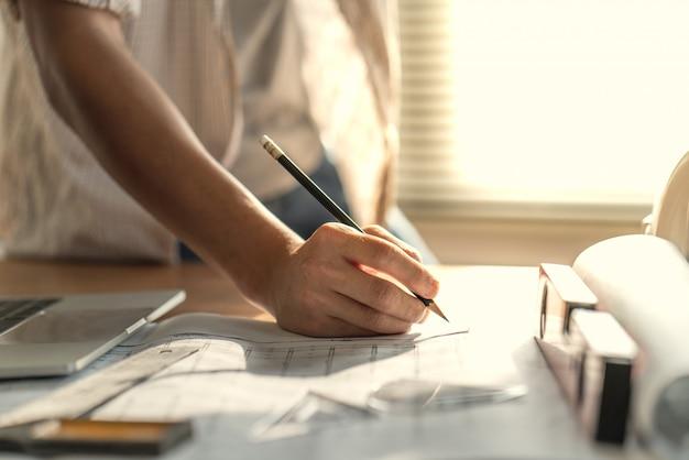 Arquiteto e engenheiro trabalhando documento de desenho sobre o planejamento do projeto e o progresso do cronograma de trabalho