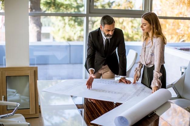Arquiteto e sua jovem colega, verificando planos e plantas
