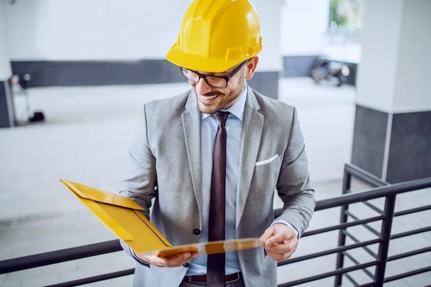 Arquiteto elegante caucasiano atraente de terno e com o capacete na cabeça, apoiando-se nos trilhos e olhando documentos na pasta.