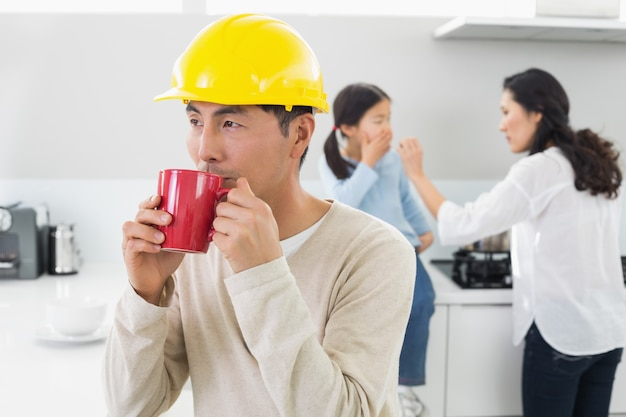 Arquiteto em chapéu duro, bebendo café com a família em segundo plano
