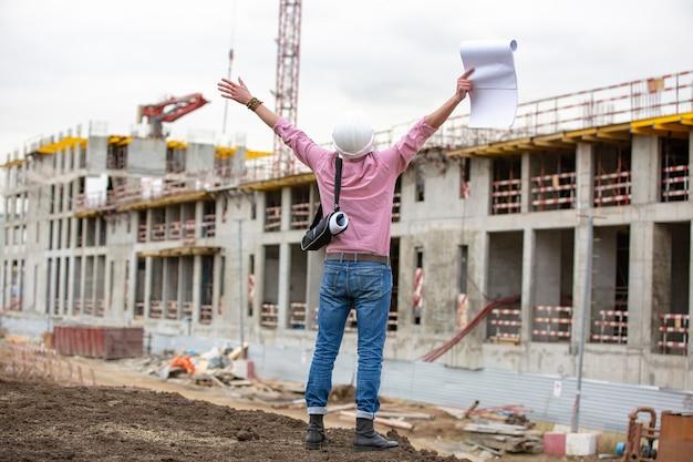 Arquiteto em um canteiro de obras comemora após o projeto de construção ter sucesso