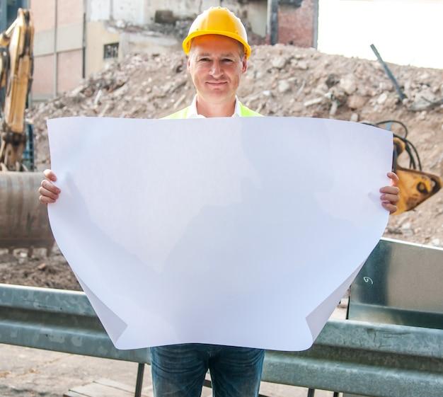 Arquiteto, engenheiro, gerente de projeto ou empresário apontam para construção na cidade com um plano em branco quanto à construção