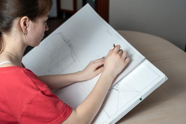 Arquiteto estudante prepara um rascunho, desenha um lápis em uma pastilha branca