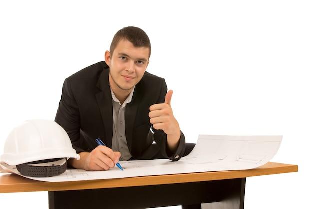 Arquiteto fazendo um gesto de sucesso com o polegar para cima enquanto se senta em uma mesa trabalhando em um plano de construção