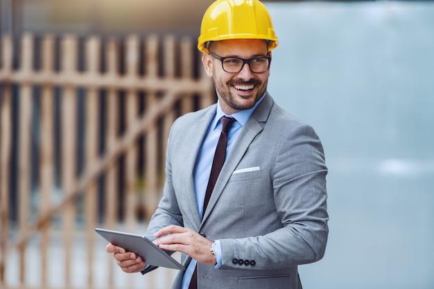 Arquiteto feliz caucasiano bonito terno cinza e com capacete amarelo na cabeça usando tablet em pé no canteiro de obras e desviar o olhar.