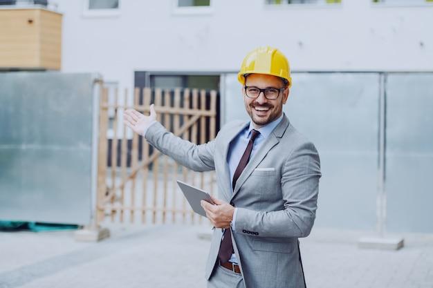 Arquiteto feliz caucasiano considerável no terno cinzento e com o capacete amarelo na cabeça que guarda a tabuleta e que mostra o canteiro de obras.