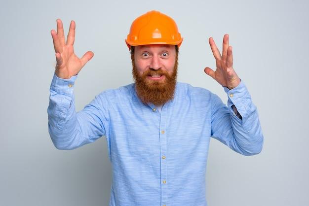 Arquiteto feliz isolado com barba e capacete laranja