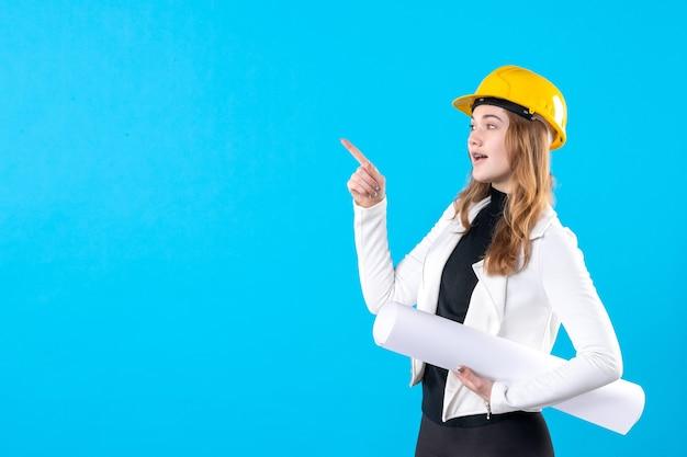 Arquiteto feminino de vista frontal com capacete amarelo segurando plano em azul