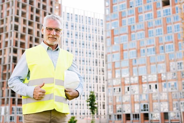 Arquiteto idoso da vista dianteira que mostra a aprovaçã0
